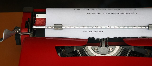 "Red typewriter with sheet of paper and the url ""www.youtube.com"" typed"