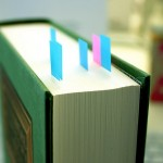 A photograph of a book with post it flags stuck in its pages.