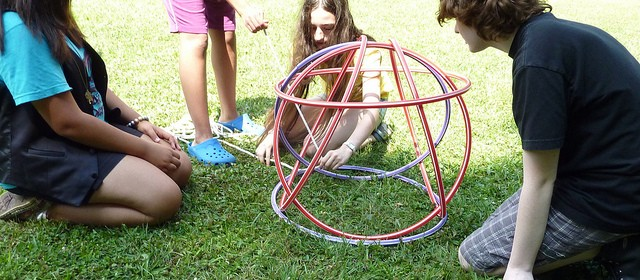 Photo of children trying a critical thinking exercise stacking hoops in complex shapes
